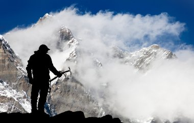 Mount Lhotse and silhouette of man wirh ice axe