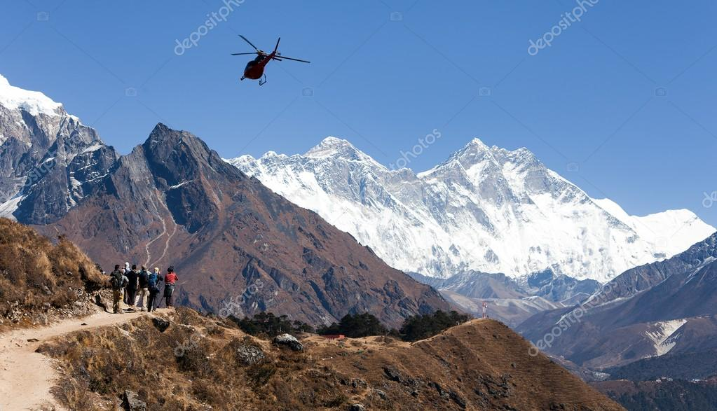 View of Everest and Lhotse with helicopter and tourists