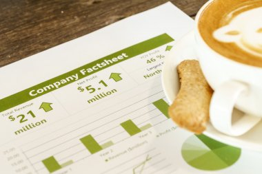 Drinking coffee while reading company financial fact sheet