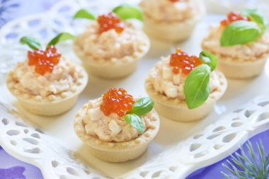 Tartlets with seafood salad, red caviar and basil