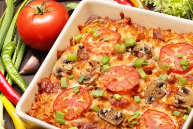 Casserole with tomato and mushrooms on a wooden background