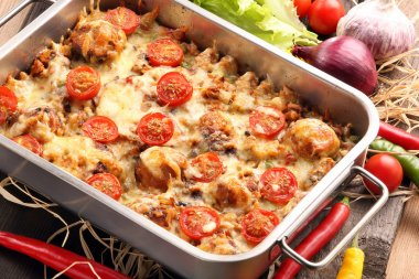 Casserole with rice meatballs and vegetables on wooden backgroun