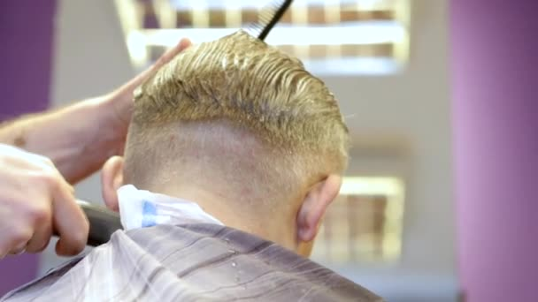 Hairdresser cutting hair by electric trimmer in slow motion
