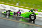 Speeding green dragster on a drag strip