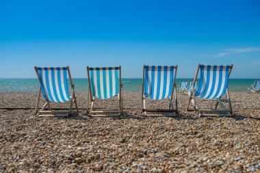 4 deck chairs on a pebble beach