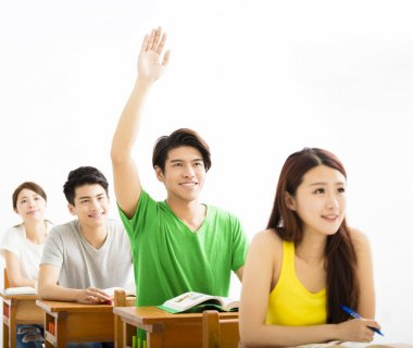college student raise hand for question in classroom