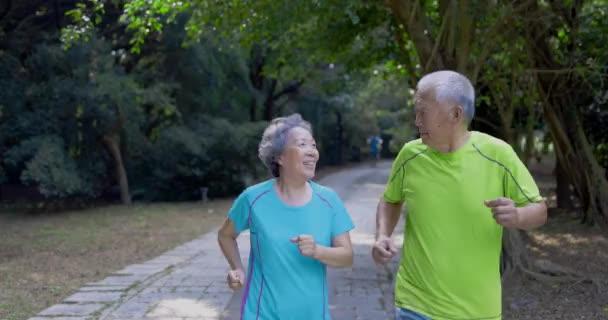 Asiatisches Senioren-Paar joggt im Naturpark