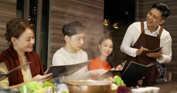 mladí přátelé s menu v teplé pot restaurace dělat objednávky
