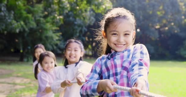 Happy Children playing reg of war at the park