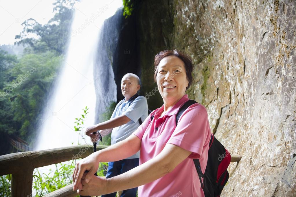 asian senior couple hiking in the mountain with waterfall