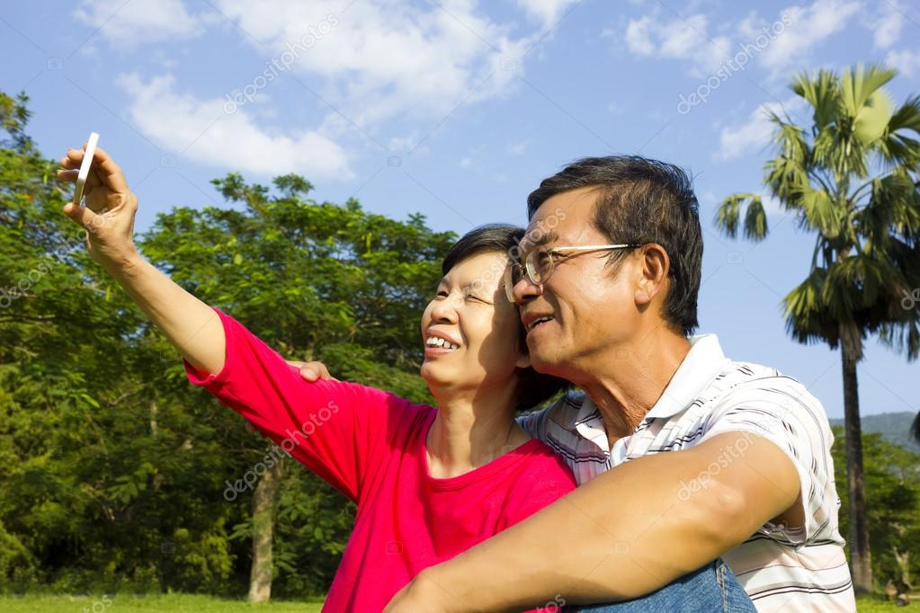 Senior couple sitting on grassland and  taking picture