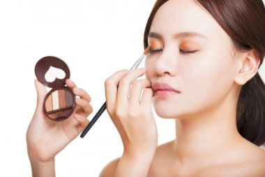 Makeup artist applying colorful eyeshadow on model's eye with a eyeshadow palettes stock vector
