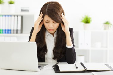 stressed  businesswoman sitting in office