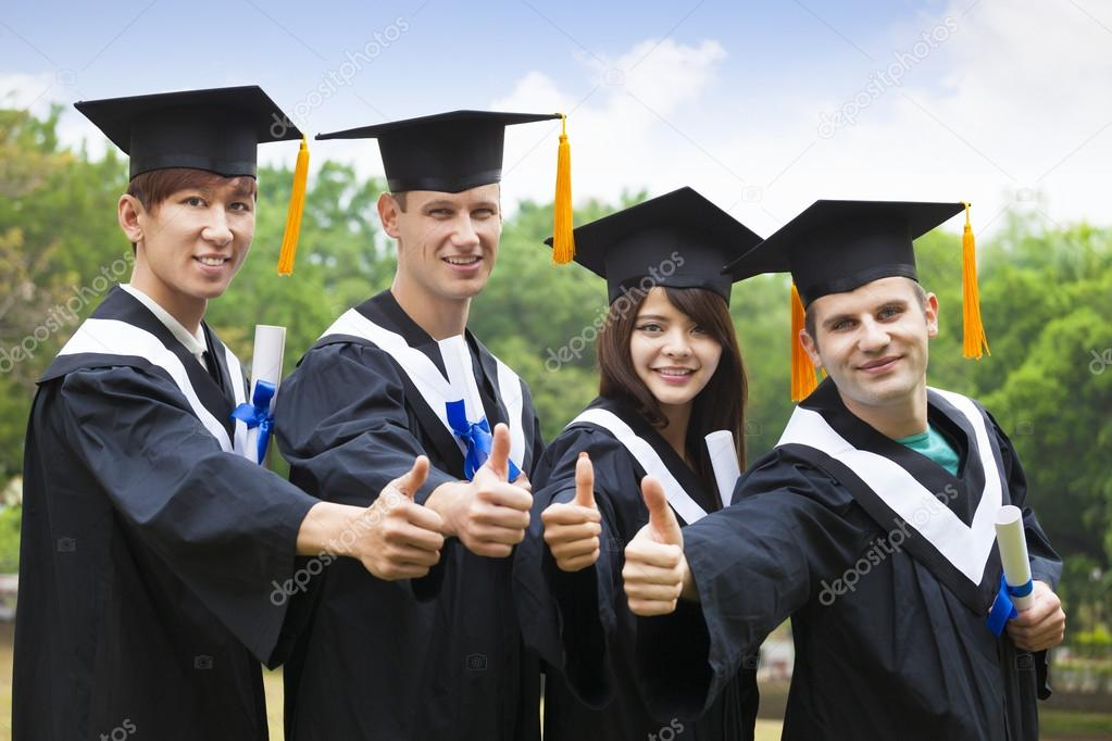 happy students in graduation gowns showing diplomas with thumbs ...