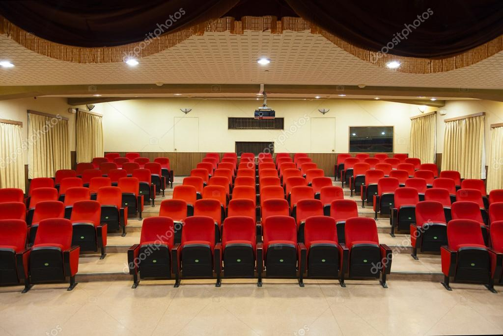 Interior of empty conference hall with red chairs