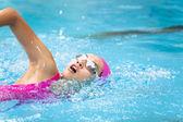 Fotografie mladé ženy je plavání v bazénu