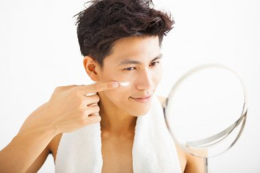 smiling man applying cream lotion on face