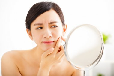 young woman Squeezing pimple looking on mirror