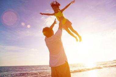 Father and little girl playing on the beach at the sunset
