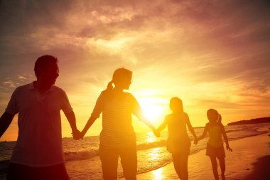 The silhouette of happy family walking on the beach
