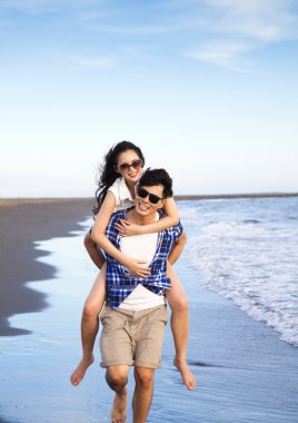 Happy young couple enjoying summer vacation on the beach