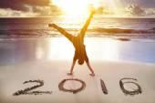 šťastný nový rok 2016. mladý muž stojka na pláži