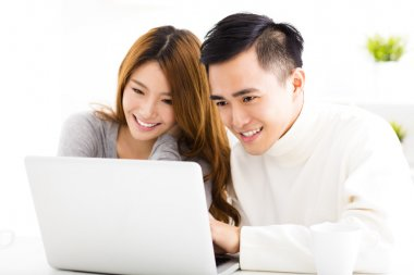 happy Asian Couple Looking at Laptop In living room