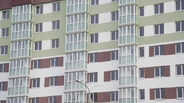 On the wall of the new residential building there are balconies and windows of apartments