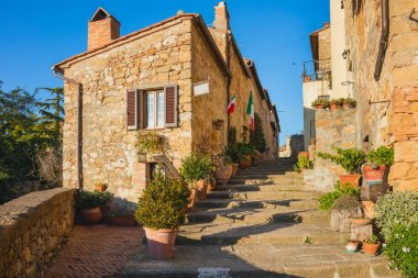 Small Old Mediterranean town - narrow street in Pienza with sunlight and flowers, Tuscany,  Italy, Europe stock vector