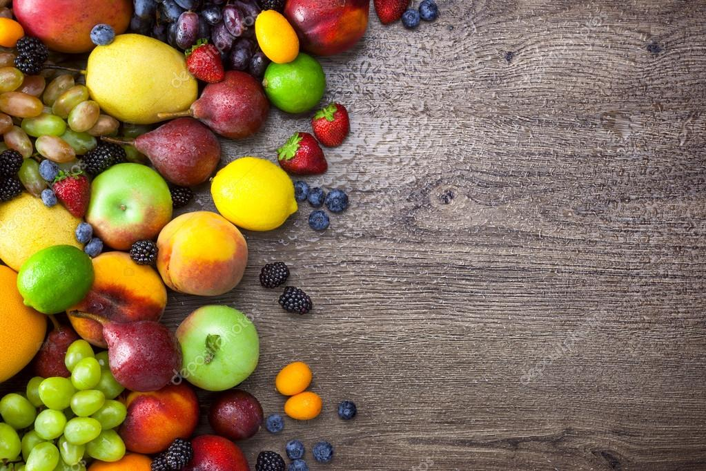 Colorful Fruits on wooden Table with water drops and copy space
