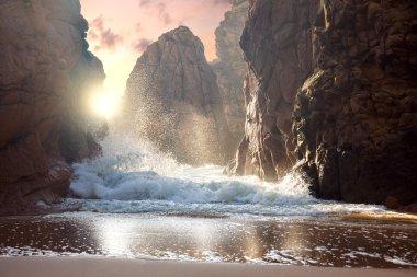 Big rocks and ocean waves at sundown
