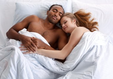 Young couple sleeping on the bed in bedroom.