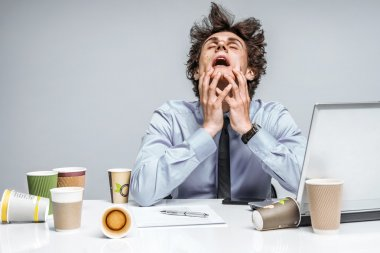 OMG! Frustrated man sitting desperate over paper work at desk.