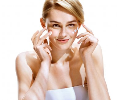 Portrait of young woman applying moisturizer cream on her pretty face.