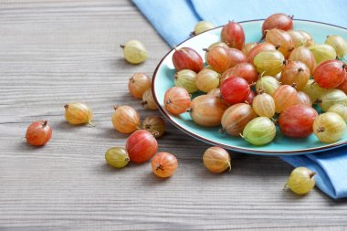 Ceramic plate with gooseberries at old wooden table.