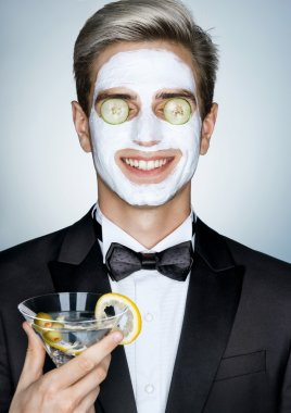Gentleman with glass of martini and cosmetic mask on the face.