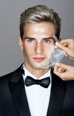Portrait of well dressed elegant man in facial mask on gray background.