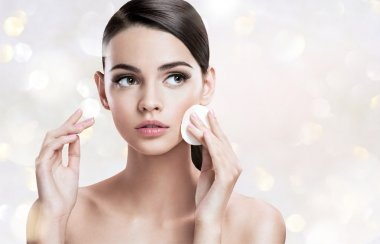 Beautiful brunette woman removing makeup from her face, skin care concept