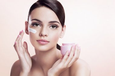 Beautiful young lady applying moisturizing creme, skin care concept