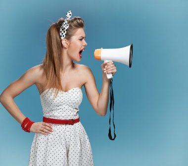 Nervous pin-up girl screaming with megaphone, mouthpiece, speaking trumpet. Filmmaking or film production concept