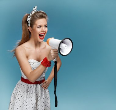 Wroth pin-up girl yells through megaphone, mouthpiece, speaking trumpet. Filmmaking or film production concept