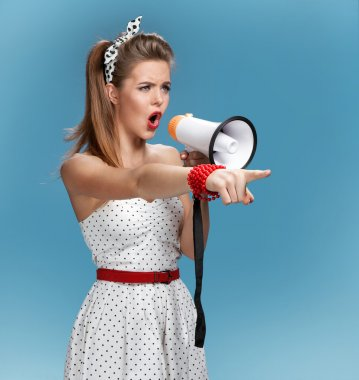 Formidable pin-up girl shouting into a megaphone, mouthpiece, speaking trumpet. Filmmaking or film production concept