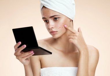 Teenager checking her face for pimple looking in the mirror. Woman with skin blemish looking at mirror isolated, beige background