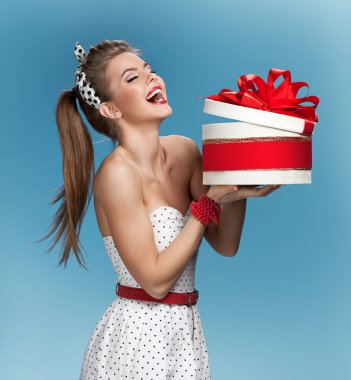Surprised laughing beautiful young woman holding an open gift box over blue background. Holidays, holiday, celebration, birthday and happiness concept