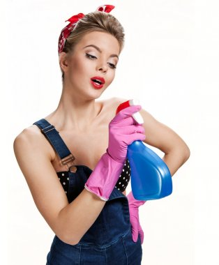 Beautiful cleaning girl wearing pink rubber protective gloves holding spray