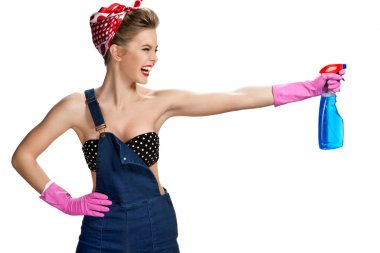 Young smiling cleaner woman wearing pink rubber protective gloves holding blue spray bottle
