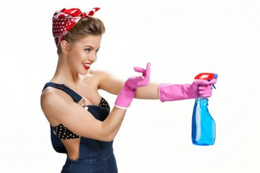 Inviting housewife wearing pink rubber protective gloves holding spray