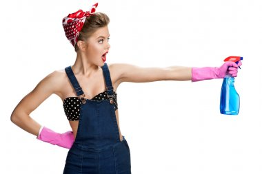 Surprised cleaning girl wearing pink rubber protective gloves holding spray