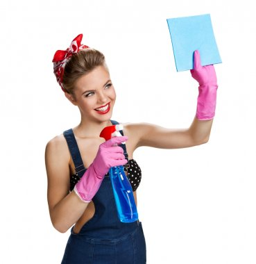 Beautiful staff wearing pink rubber protective gloves holding cleaning spray bottle and cellulose sponge