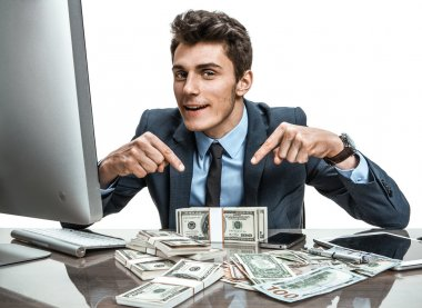 Modern businessman at his desk with computer and a lot of money